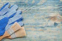 Raccolta dei guanti protettivi dei pennelli sul raggiro del bordo di legno Fotografie Stock Libere da Diritti