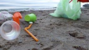 Raccolta dei rifiuti sulla spiaggia Plastica e pacchetti sparsi sulla spiaggia Un uomo raccoglie di plastica Concetto di protezio stock footage
