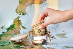 Raccolta dei soldi per il viaggio Latta di vetro come salvadanaio con contanti Immagine Stock