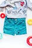 Raccolta dei vestiti e dei giocattoli per la vista superiore del fondo bianco della stanza di bambino Immagini Stock Libere da Diritti
