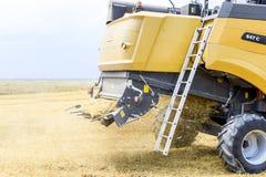 Raccolta del grano con una mietitrebbiatrice Fotografie Stock Libere da Diritti