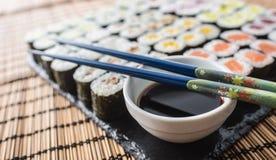 Raccolta del maki dei sushi sul bordo dell'ardesia con la salsa ed i tagli di soia Fotografia Stock Libera da Diritti