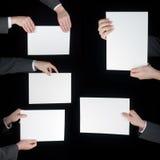 Raccolta della mano che tiene carta in bianco sul nero Immagine Stock