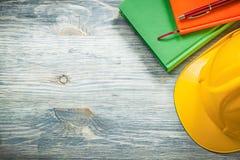 Raccolta della penna dei blocchi note del casco della costruzione sul constru di legno del bordo Fotografia Stock