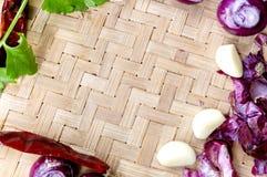 Raccolta delle cipolle e dei chilis freschi sul bambù opaco Immagine Stock