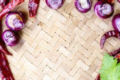 Raccolta delle cipolle e dei chilis freschi sul bambù opaco Fotografie Stock