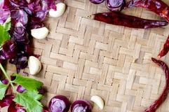 Raccolta delle cipolle e dei chilis freschi sul bambù opaco Immagini Stock