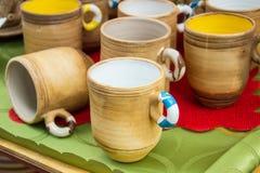 Raccolta delle tazze variopinte da vendere al bazar, accessori della cucina Fotografia Stock