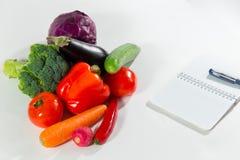 Raccolta e taccuino della verdura fresca con il piano di dieta isolati su fondo bianco Fotografie Stock