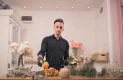 Raccolto del fiorista che sceglie sistemando i fiori, negozio di fiore all'interno Fotografia Stock