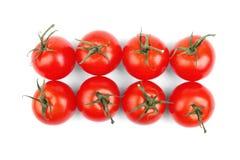 Raccolto di estate dei pomodori rossi luminosi con le foglie verdi su un fondo bianco verdure Pomodori succosi, maturi e freschi Immagine Stock Libera da Diritti