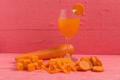 Raccord en caoutchouc coupé en tranches cube avec la carotte en verre de jus sur le rose en bois Images stock