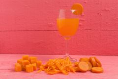 Raccord en caoutchouc coupé en tranches cube avec la carotte en verre de jus sur le rose en bois Photographie stock