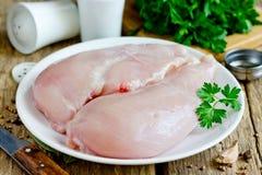 Raccordi crudi del petto di pollo sul piatto sulla tavola di legno fotografia stock libera da diritti