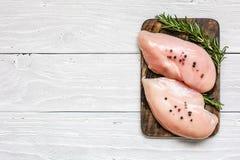 Raccordi crudi del petto di pollo sul tagliere di legno con le erbe e le spezie immagini stock libere da diritti