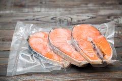 Raccordi di color salmone congelati in un imballaggio sotto vuoto immagini stock