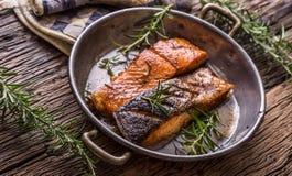 Raccordi di color salmone grezzi Salmone arrostito, decorationon dell'erba dei semi di sesamo sulla pentola d'annata o bordo nero immagine stock libera da diritti