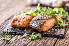 Raccordi di color salmone grezzi Salmone arrostito, decorationon dell'erba dei semi di sesamo sulla pentola d'annata o bordo nero fotografie stock libere da diritti