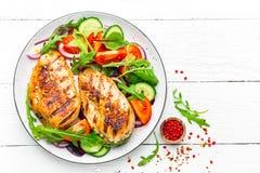 Raccordo arrostito del pollo fritto del petto di pollo ed insalata della verdura fresca dei pomodori, dei cetrioli e delle foglie fotografia stock libera da diritti
