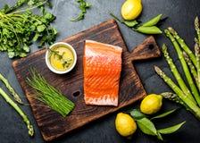 Raccordo, asparago, limoni ed erbe di color salmone crudi sul bordo di legno Alimento che cucina fondo con lo spazio della copia  Fotografia Stock Libera da Diritti
