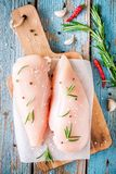 Raccordo crudo del pollo con aglio, pepe e rosmarini su fondo rustico Fotografie Stock Libere da Diritti