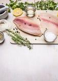 Raccordo crudo di tilapia con le spezie ed erbe, limone e pepe su un tagliere un villaggio rustico del fondo bianco Fotografia Stock