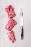 Raccordo crudo tagliato della carne di maiale con il coltello della carne Fotografia Stock