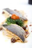 Raccordo del branzino con i ravioli, gli spinaci e le olive Fotografia Stock