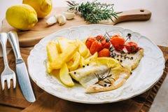 Raccordo del pesce con le patate, pomodori ciliegia Immagine Stock Libera da Diritti