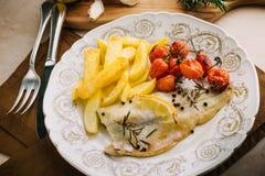 Raccordo del pesce con le patate, pomodori ciliegia Fotografie Stock Libere da Diritti