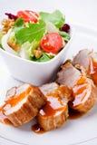 Raccordo della carne di maiale con insalata Fotografia Stock