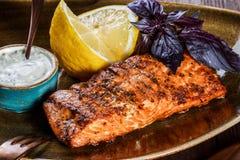 Raccordo di color salmone al forno con la salsa, il basilico ed il limone di formaggio sul piatto su fondo di legno immagini stock