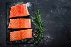Raccordo di color salmone crudo sul fondo scuro dell'ardesia, pesce atlantico selvaggio, spazio per testo fotografia stock libera da diritti