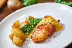 Raccordo di color salmone grigliato avvolto nei cunei della patata e del bacon sul piatto bianco fotografia stock libera da diritti
