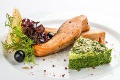 Raccordo fritto del salmone con spinaci Su un piatto bianco fotografie stock