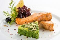 Raccordo fritto del salmone con spinaci Su un piatto bianco fotografia stock