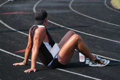 After the Race. Triathlete sitting on track after the race Stock Image