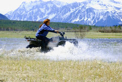 Race. A woman racing an ATV through the water stock photos
