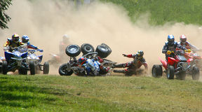 Race ATV Motocross. This was taken at a motocross event of participants going into the first turn, in which a couple of them took a spill Stock Images