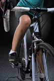Race bike closeup with legs of female biking athlete Stock Photo