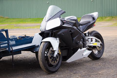 Race Bike at Rest # 2. A modern racing superbike leaning against its trailer in the paddock at a racetrack Stock Images