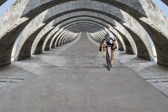 Race Biker Approaches Under Concrete Arcades Royalty Free Stock Images
