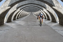 Race biker approaches under concrete arcades. Front view of race biker who rides his bike under floating concrete light flooded arcades Royalty Free Stock Images