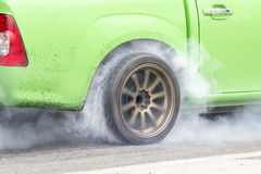 Race car burns rubber off its tires Stock Images