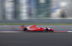 Race car racing at high speed in the city. Formula 2.0 race car racing at high speed with motion blur on the background of the city in the day Royalty Free Stock Photo