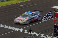 Race car racing on speed track. With motion blur crossing finish line stock photography
