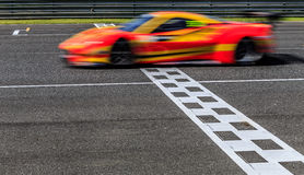 Race car racing on speed track. With motion blur crossing finish line Stock Photos