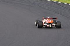 Race car on track. An orange race car on a track royalty free stock photo