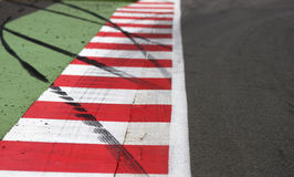 Race Circuit Edge. Brightly painted edge markings on a motor racing circuit, with overlaid black rubber tyre markings. Clear area on the right is ideal for text Stock Image