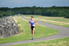 Race. Contestant in the Vitruvian triathlon (comprising a 1900m swim, a 85 km bike ride and a 21 km run) at Rutland Water on Saturday 29 August 2015 stock photos